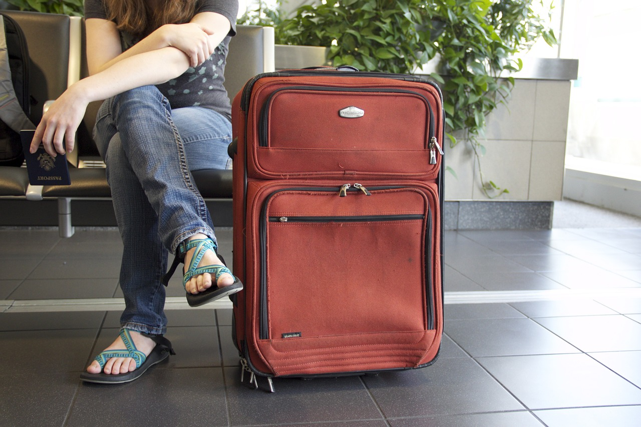 A person wearing jeans and sandals waits in the airport with their large red suitcase.