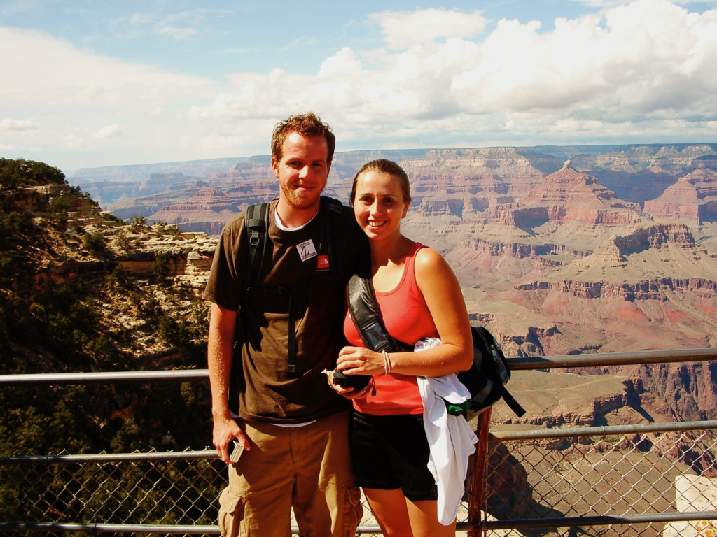 A young couple standing in front of a large canyon.