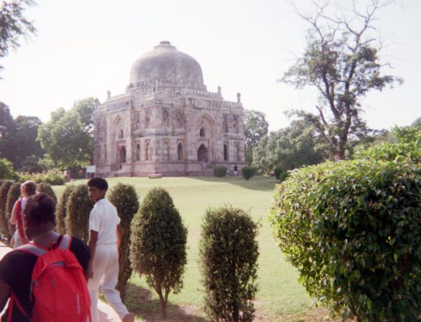People walking by temple and garden in India